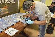 Сотрудник полиции Аргентины открывает пакет с кокаином, обнаруженный в одном из зданий посольства России в Буэнос-Айресе, 22 февраля