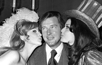 """Мисс Великобритания Мэрилин Энн Уорд и Мисс США Брюсин Смит целуют Роджера Мура в Лондонском отеле Savoy. Фото было сделано в преддверии конкурса """"Мисс Мира"""", ноябрь 1971 года"""