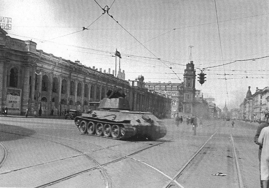 Танк Т-34, направляющийся на передовую(Угол проспекта 25-го Октября и улицы 3-го Июля).Витрины Гостиного двора заложены досками