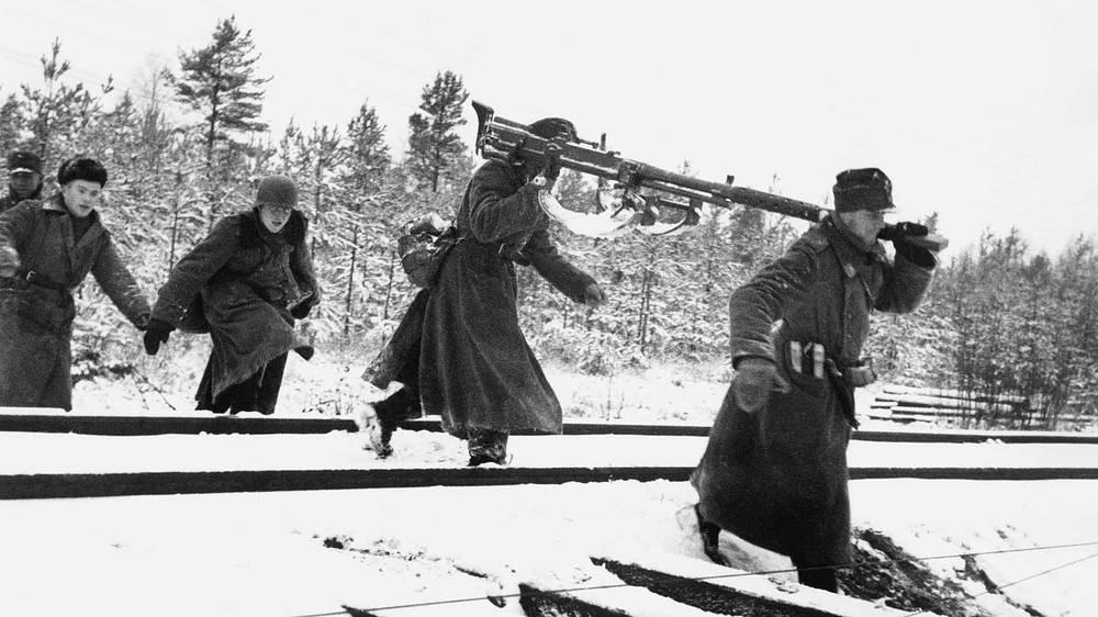 Финские солдаты переносят 20-мм противотанковое ружье VKT L-39 через железнодорожную насыпь, 1941 год