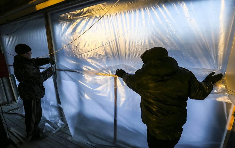 Челябинская область. Люди заклеивают полиэтиленом окна, выбитые взрывной волной, вызванной падением метеорита