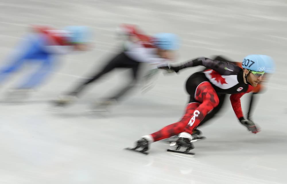 Канадский шорт-трекист Оливье Жан (слева) во время олимпийского турнира по шорт-треку на дистанции 1000 м