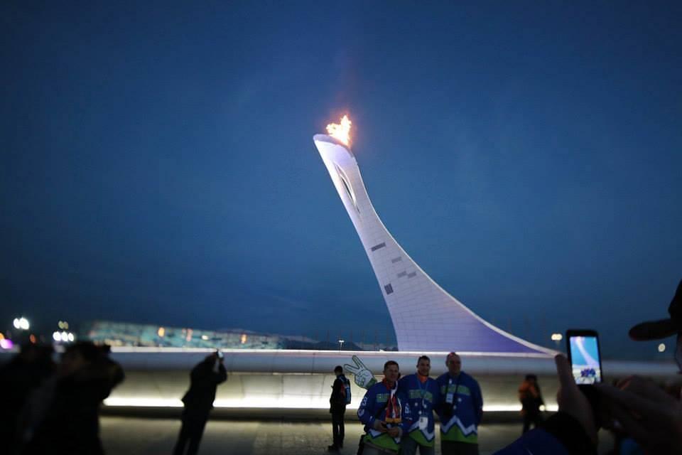 Болельщики фотографируются на фоне чаши олимпийского огня в Олимпийском парке