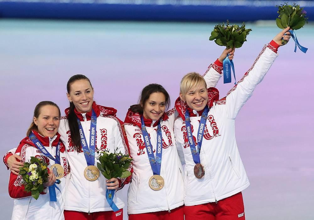 Ольга Граф, Екатерина Лобышева, Екатерина Шихова и Юлия Скокова (слева направо), завоевавшие бронзовые медали в командной гонке преследования на соревнованиях по конькобежному спорту среди женщин на XXII зимних Олимпийских играх.