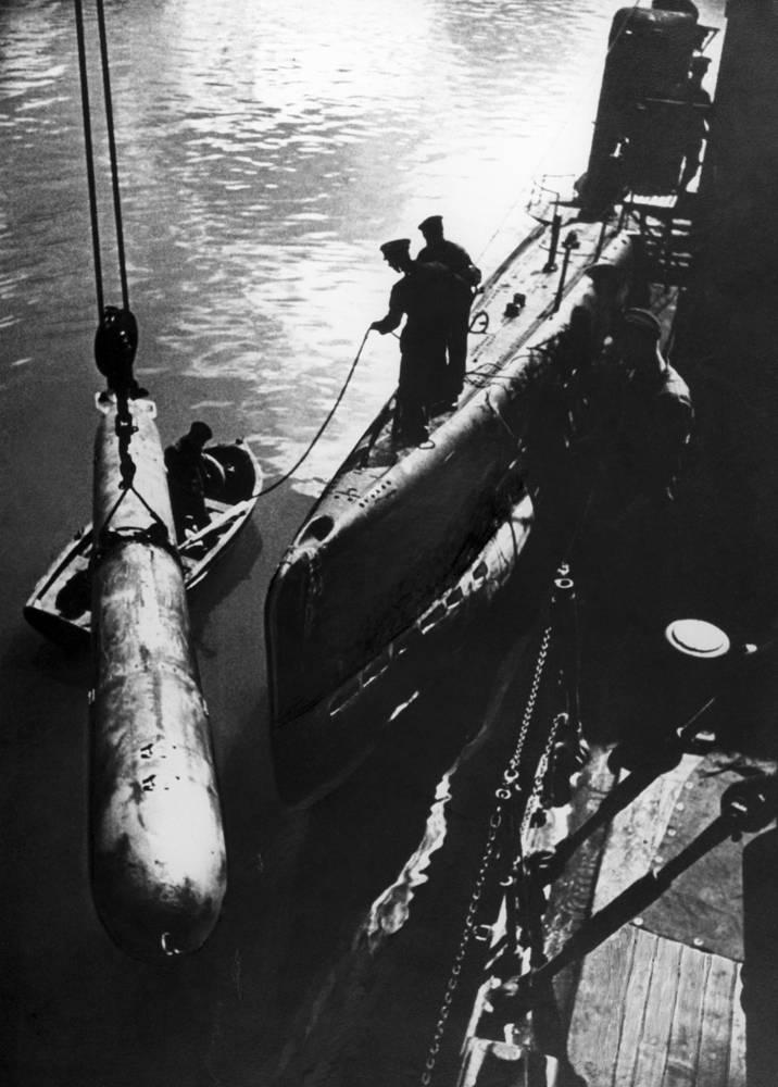 """Нападение фашистской Германии Черноморский флот встретил в полной боевой готовности. На фото: экипаж подводной лодки М-117 загружает с плавбазы """"Эльбрус"""" торпеды перед выходом на боевую операцию, 1943 год"""