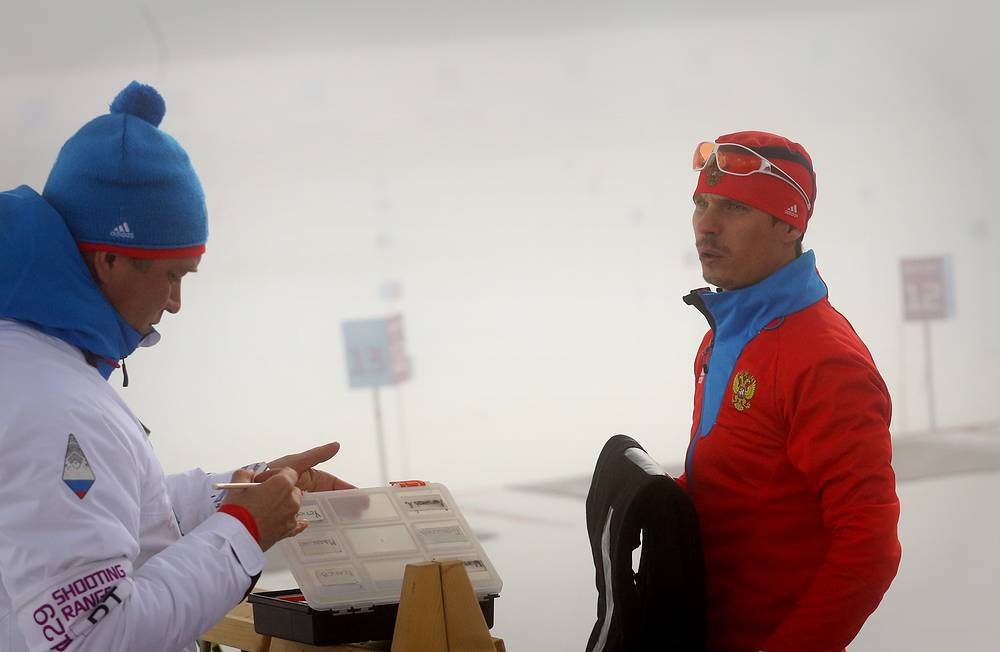 Евгений Устюгов (справа) перед началом гонки на соревнованиях по биатлону на XXII зимних Олимпийских играх