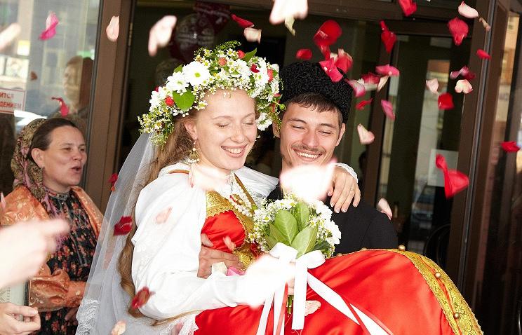 Жених и невеста в традиционных костюмах на современной свадьбе