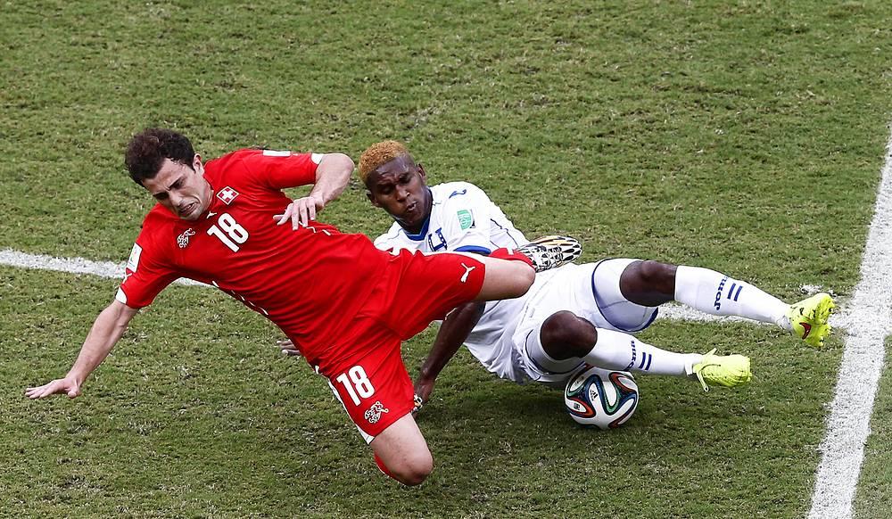 Защитник сборной Гондураса Брайан Беккелес в стыке с форвардом швейцарцев Адмиром Мехмеди