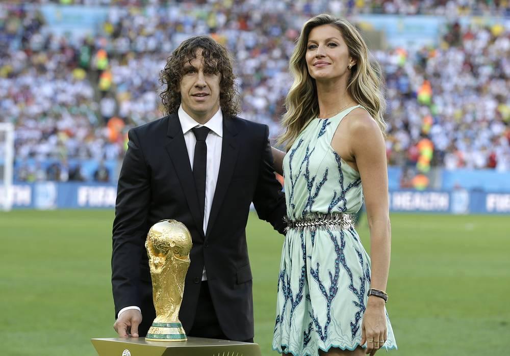 Бывший капитан сборной Испании Карлес Пуйоль и модель Жизель Бюндхен с Кубком мира ФИФА