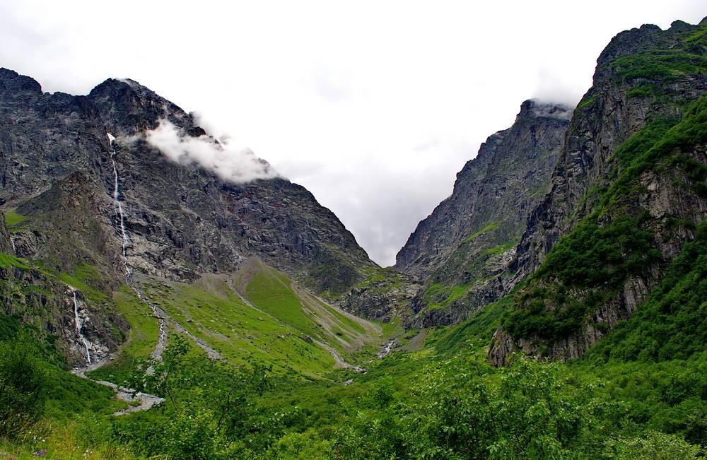 Стоять на дне огромной чаши, по скальным стенам которой срываются ревущие водопады, — зрелище фантастическое. У самого основания водопада можно заметить тот самый ледник, из-под которого рождается знаменитый Зейгалан.