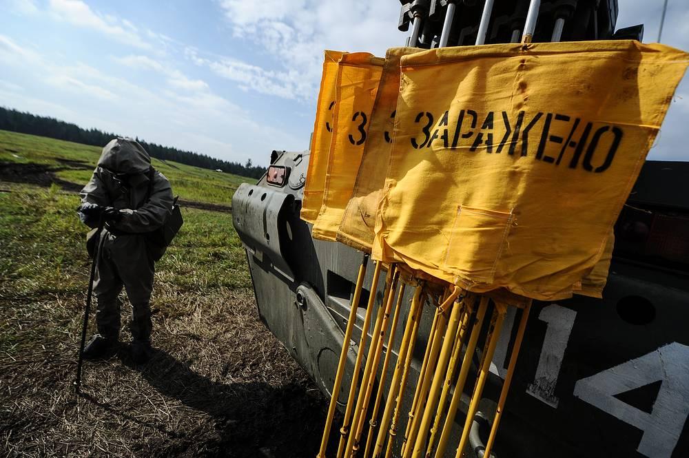 Военнослужащий осуществляет дозиметрический и химический контроль почвы во время лагерного сбора