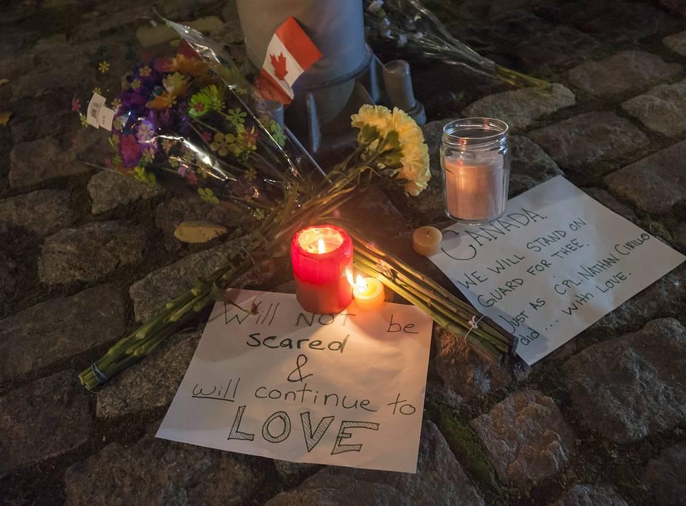 Цветы и свечи возле военного мемориала в Оттаве