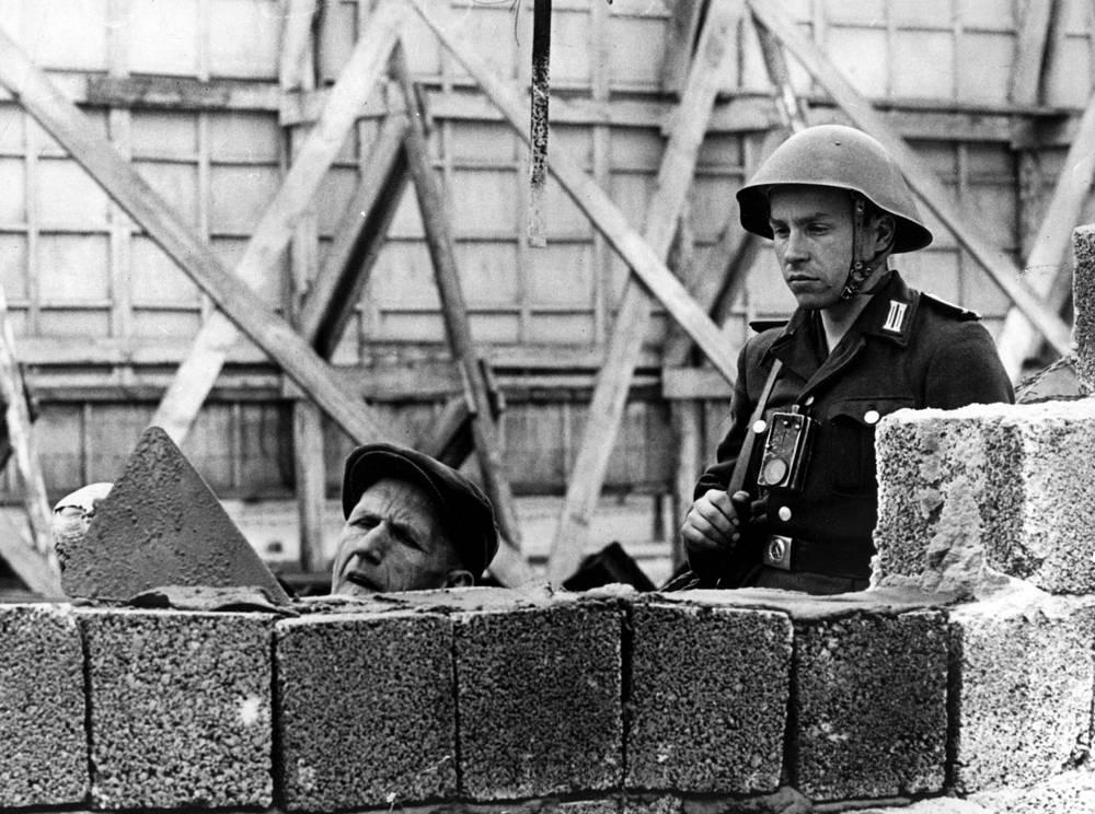 Общая длина стены превышала 111 км, высота достигала 3,6 м, а толщина - 1,5 м. На фото: солдат Национальной народной армии ГДР (справа) курирует рабочих, достраивающих разделительную стену в районе улицы Бернауэрштрассе, 1962 год
