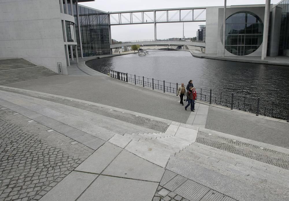 Туристы пересекают линию Берлинской стены, отмеченную каменной вкладкой
