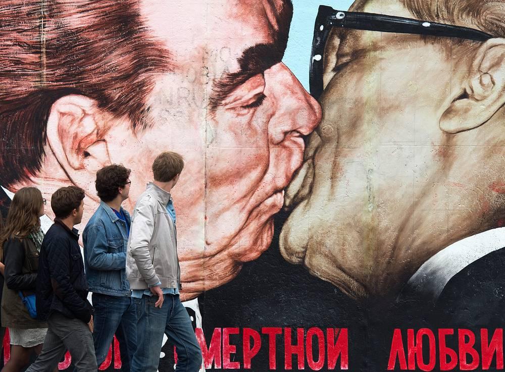 """Берлинская стена была разбита и расписана многочисленными граффити, рисунками и надписями. На фото: граффити Дмитрия Врубеля """"Господи! Помоги мне выжить среди этой смертной любви"""", изображающее поцелуй генерального секретаря ЦК КПСС Леонида Брежнева и руководителя ГДР Эриха Хонеккера"""