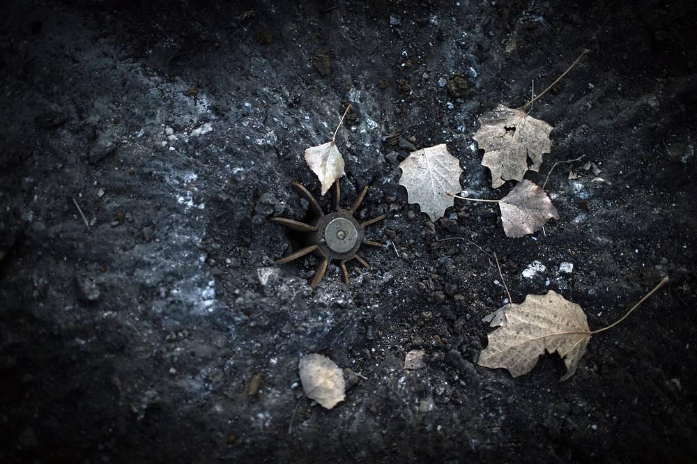 По тротуару одной из центральных улиц Первомайска прогуливаются двое - отец и сын. Они подбирают с земли свежие осколки и рассматривают их. Метрах в двадцати от них из асфальта торчит хвост неразорвавшейся мины. На фото: стабилизатор мины на одной из улиц города