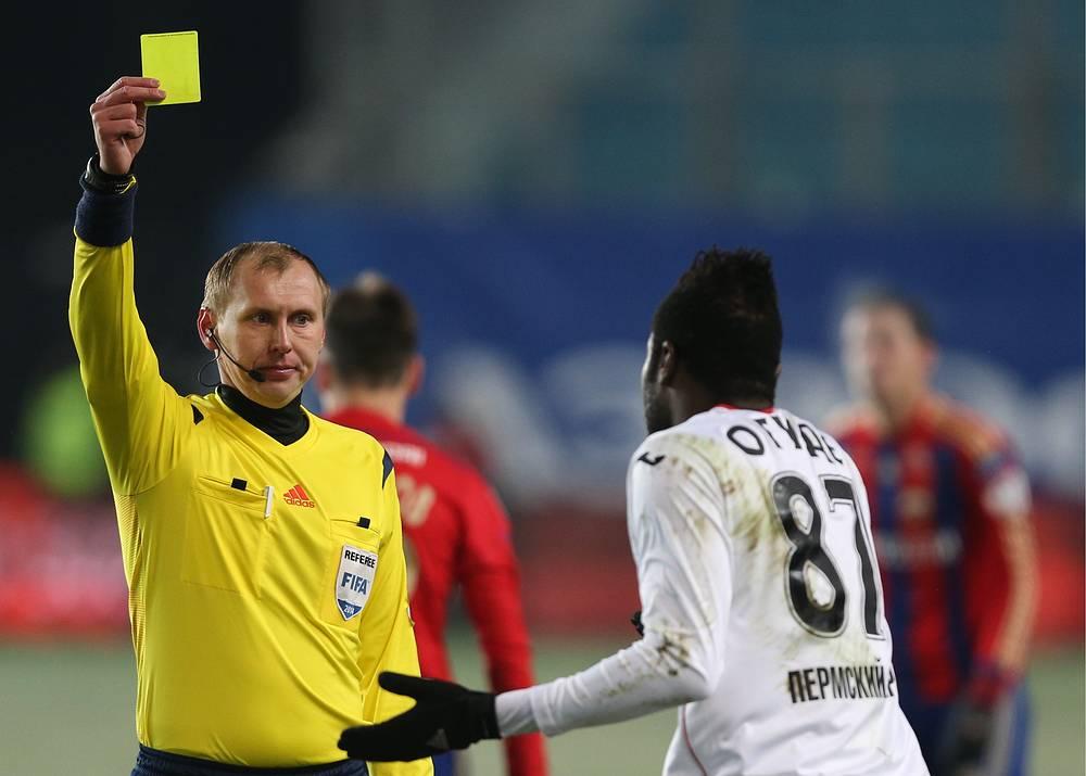 """Игрок """"Амкара"""" Фегор Огуде (справа) получает желтую карточку"""