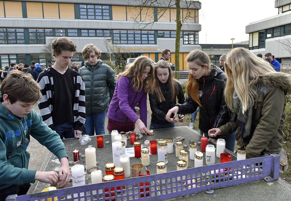 Школьники оставляют свечи на столе для настольного тенниса перед зданием гимназии в городе Хальтерн-ам-Зе, Германия