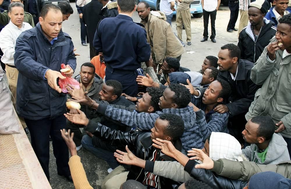 Еще два судна перевозившие, в общей сложности, около 500 человек (из них около 200 - граждане Нигерии), обнаружить не удалось. На фото: ливийский полицейский раздает хлеб выжившим после кораблекрушения, 29 марта 2009 года