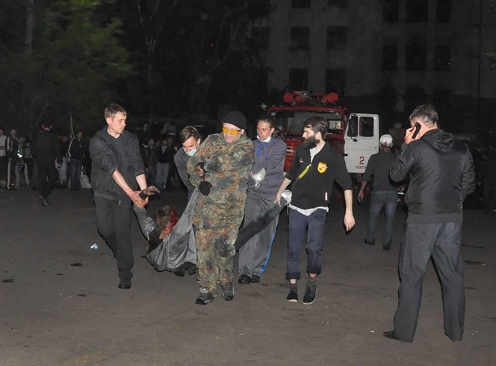 Люди выносят пострадавшего при пожаре в Доме профсоюзов, Одесса, 2 мая 2014 года