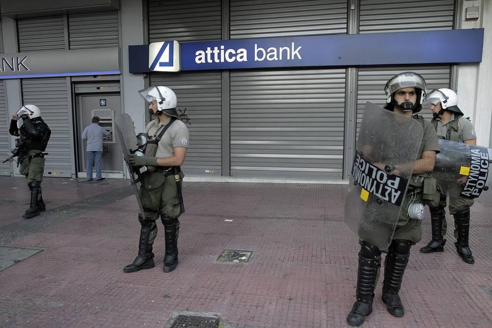 Всего с конца ноября частные депозиты в греческих банках снизились на €44 млрд  до €120 млрд, отмечает издание со ссылкой на международное рейтинговое агентство Moody's. На фото: полиция около банкоматов в Афинах