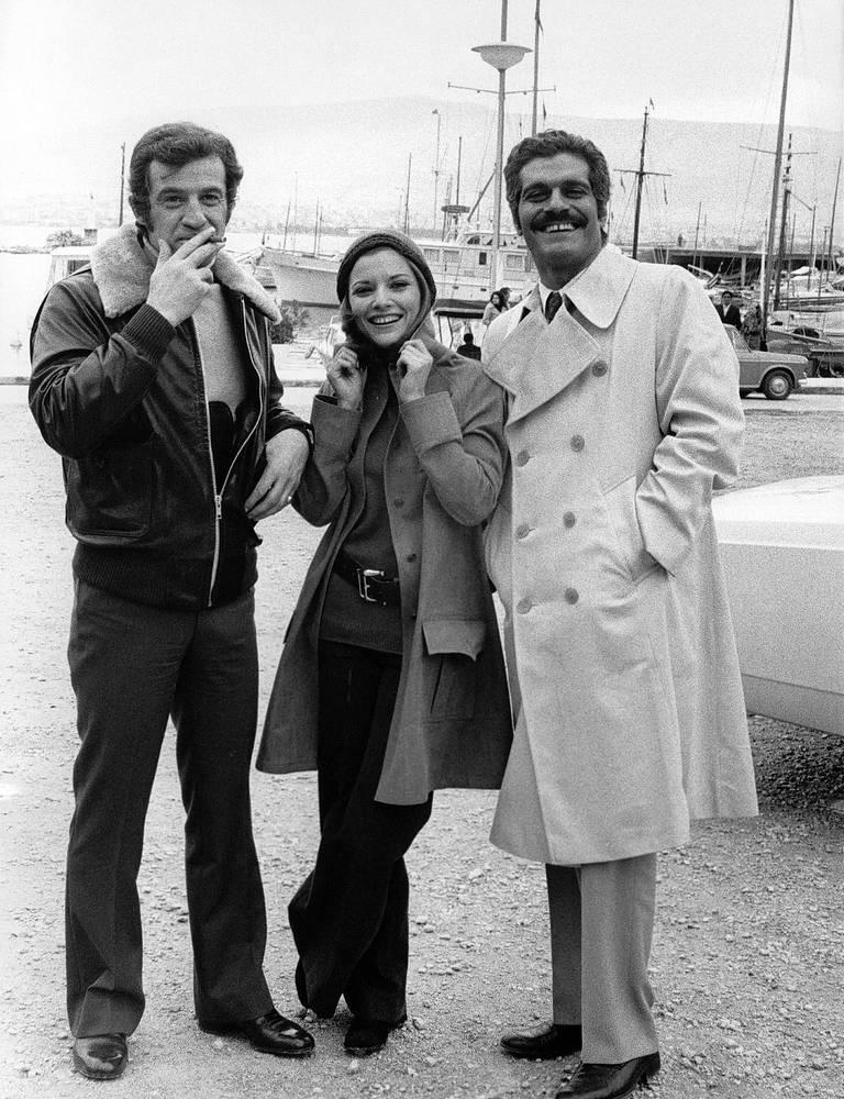 """Актеры Жан-Поль Бельмондо (слева), Николь Кальфан и Омар Шариф на съемках фильма """"Взломщики"""" в Пирее, Греция, 19 февраля 1971 года"""
