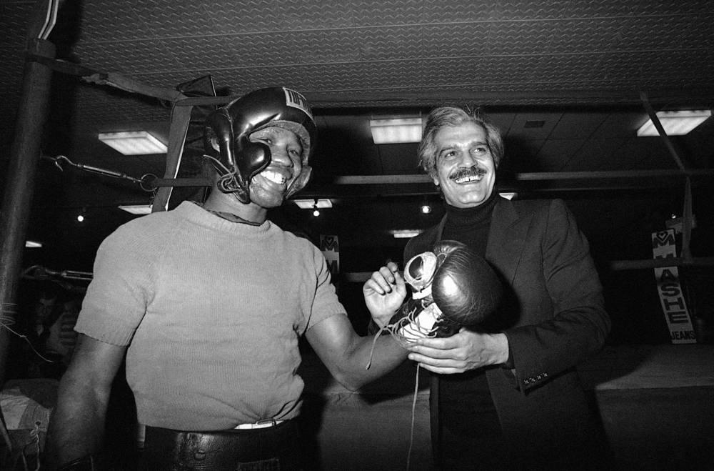 Омар Шариф зашнуровывает перчатки чемпиону мира в среднем весе по версии WBC колумбийцу Родриго Вальдесу. Париж, 23 марта 1976 года