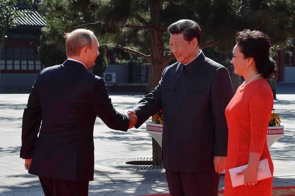 Президент РФ Владимир Путин, председатель КНР Си Цзиньпин с супругой Пэн Лиюань на церемонии встречи гостей, прибывших на парад