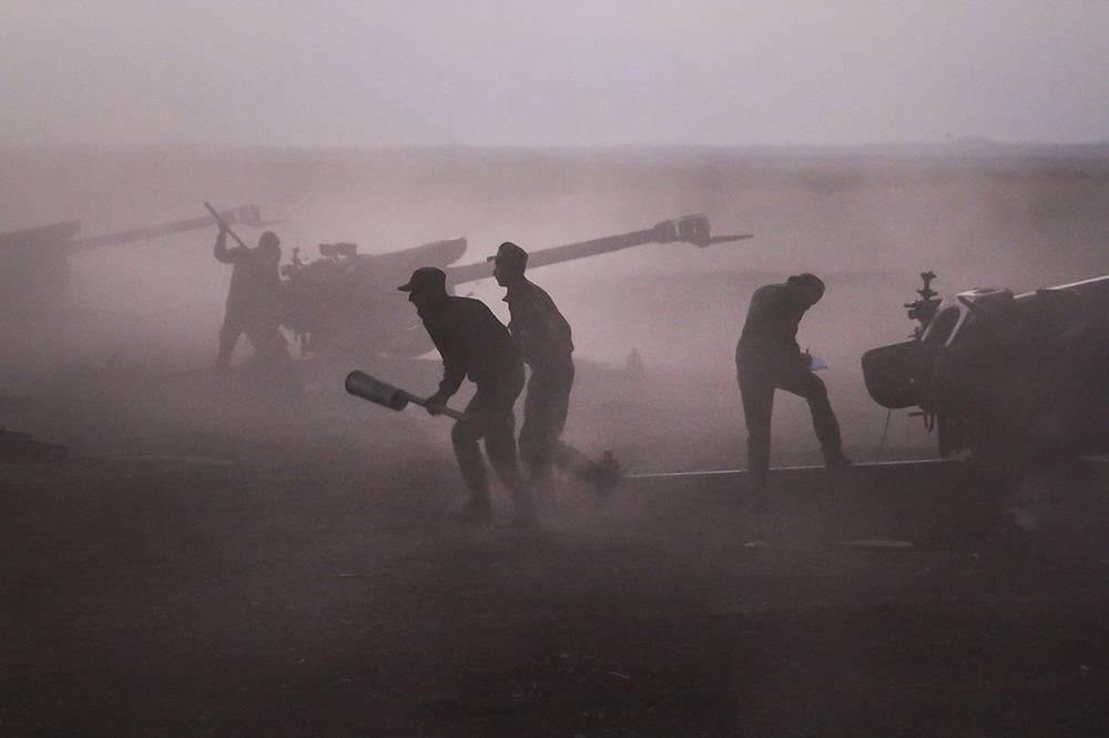 Сирийские военнослужащие заряжают гаубицы неподалеку от города Морек в Сирии, 7 октября