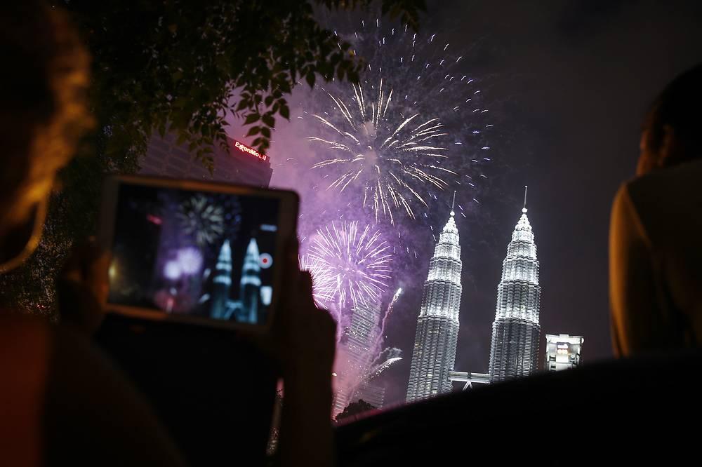 Куала-Лумпур. Малайзия. 1 января 2016. Жители города наблюдают за салютом напротив Башни Петронас.