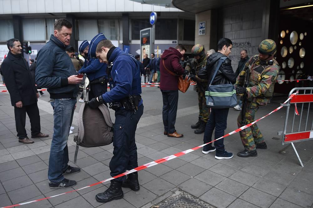 """Сотрудник полиции и военнослужащие во время досмотра пассажиров у входа на станцию метро """"Де Брукер"""""""