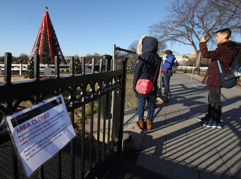 Туристы смотрят на главную рождественскую ель США, доступ к которой закрыт, Вашингтон