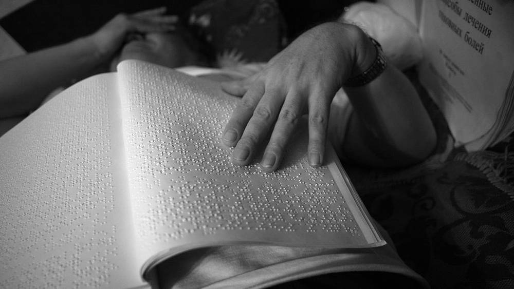 Александр Суворов читает книгу для слепых.  Фото ИТАР-ТАСС/Сергей Шахиджанян