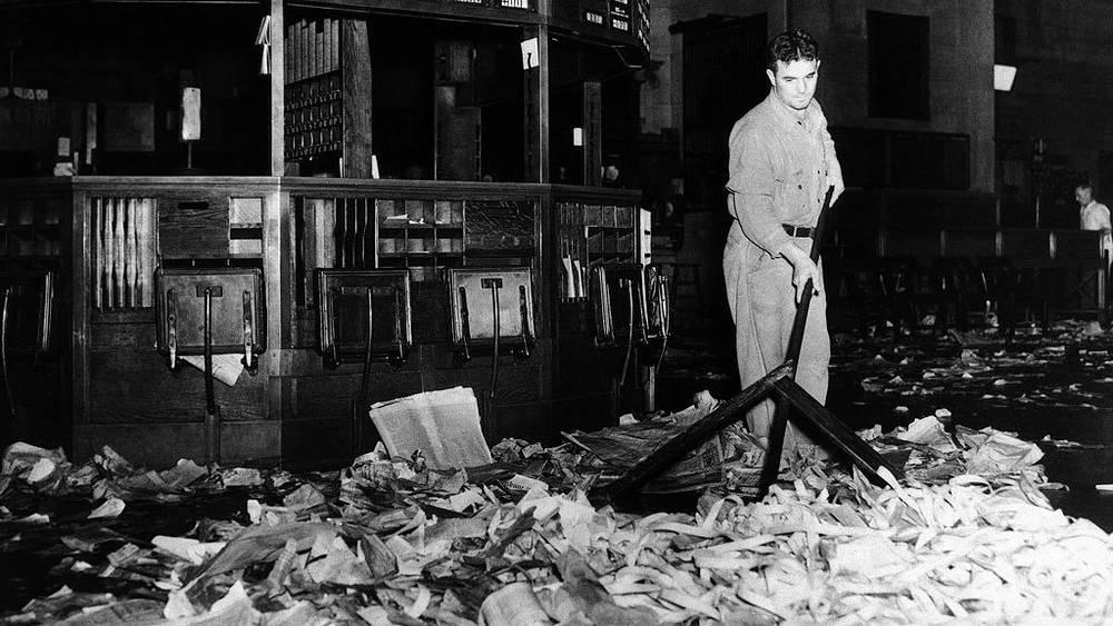 Уборщик очищает нью-йоркскую биржу  от мусора. 24 октября 1929 года. Фото АР