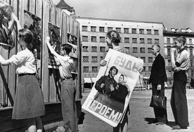 Школьники развешивают плакаты на улице