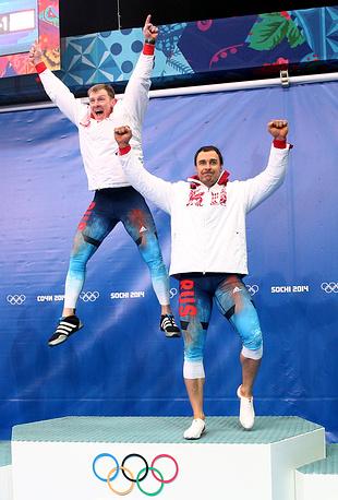 Российские спортсмены Александр Зубков, Алексей Воевода (слева направо), завоевавшие золото, во время цветочной церемонии на соревнованиях двоек по бобслею