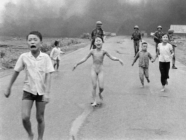 """Фотография американского фотографа Ника Ута """"Напалм во Вьетнаме"""" - один из самых известных снимков о вьетнамской войне. На фото: мирные жители бегут от атаки напалмовыми бомбами южновьетнамских ВВС, 8 июня 1972 года"""