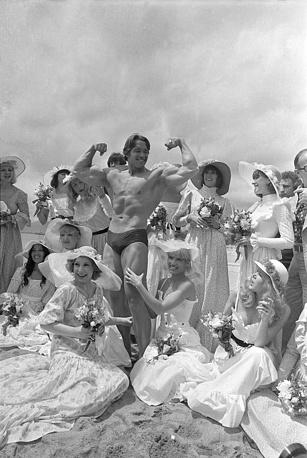 Арнольд Шварценеггер демонстрирует мускулы девушкам на пляже, 1977 год
