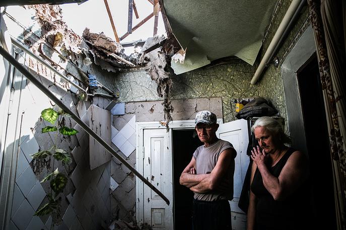 Обстрел начался в понедельник вечером и возобновился во вторник утром. На фото: жители Славянска в разрушенном доме