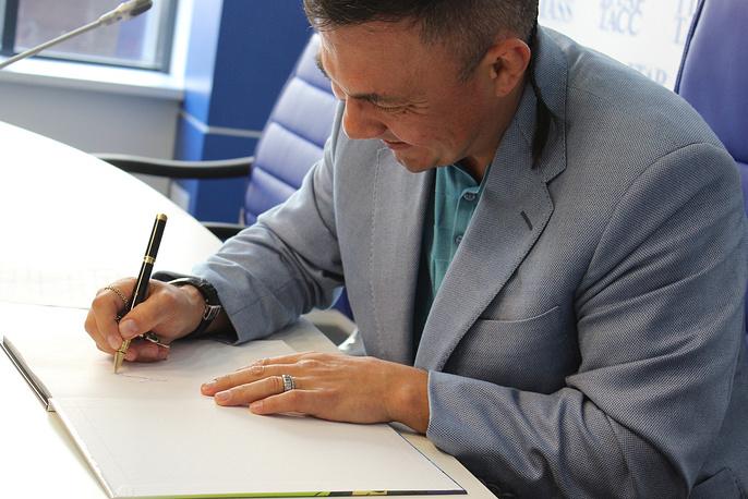 Константин Цзю подписывает книгу