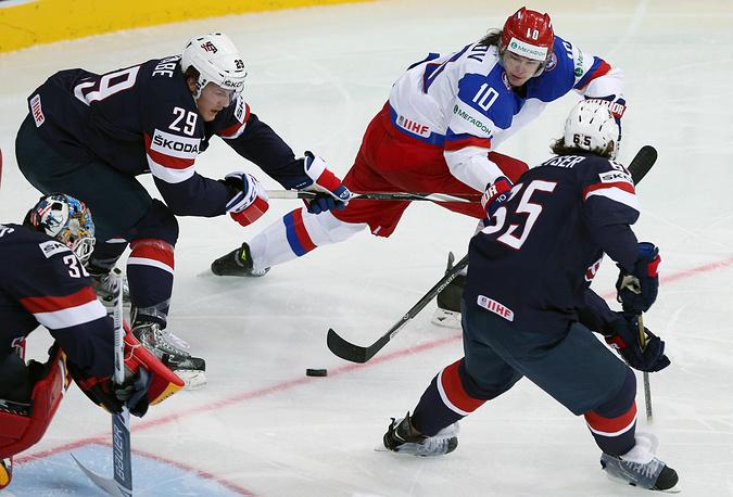 Игроки сборной США вратарь Тим Томас, Джейк Маккейб (слева направо), Дэнни Декайзер (справа) и России Виктор Тихонов (второй справа) в матче чемпионата мира по хоккею: Россия - CША