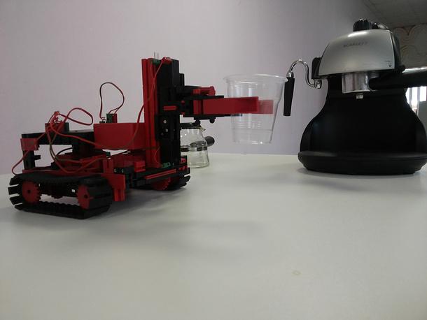 Гусеничный робот подвозит стакан к кофеварке
