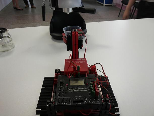 Гусеничный робот забирает стакан из-под кофеварки