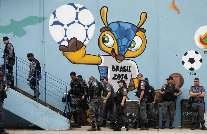"Полицейские возле граффити с изображением талисмана чемпионата мира по футболу-2014 недалеко от стадиона ""Маракана"" в Рио-де-Жанейро"