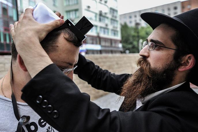 В иудаизме частью молитвенного облачения является тфилин - небольшие коробочки из кожи, содержащие отрывки Священного Писания и прикреплённые к ремням, которые наматываются на голову и на левую руку