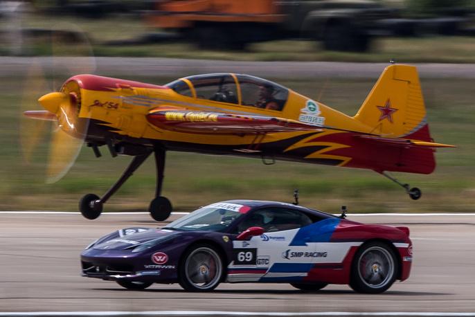 Учебно-тренировочный самолет Як-54 и суперкар Ferrari 458 Italia во время шоу
