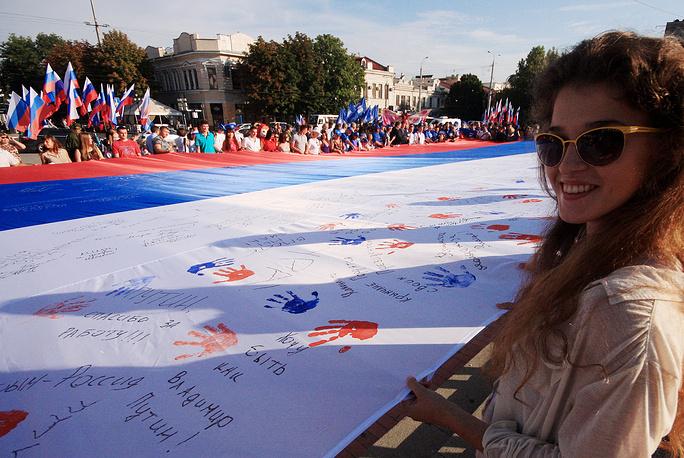 22 августа в России отметили День государственного флага. На фото: жители Симферополя во время празднования на площади перед зданием Госсовета Республики Крым