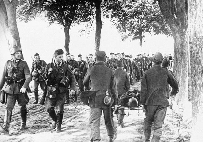 Немецкие солдаты идут навстречу польским военнопленным, несущим своего раненого товарища. 6 сентября 1939 года