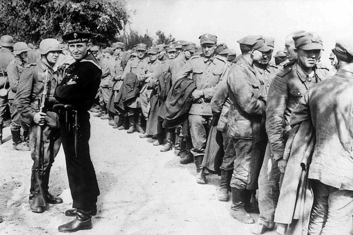 Немецкие пехотинец и морпех охраняют сдавшийся польский гарнизон в окрестностях Данцига. 3 сентября 1939 года
