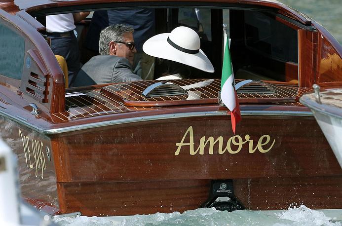 """Частное водное такси с надписью """"Любовь"""", на котором передвигаются Клуни и Аламуддин, """"эскортируют"""" десятки лодок с папарацци и просто любопытными"""